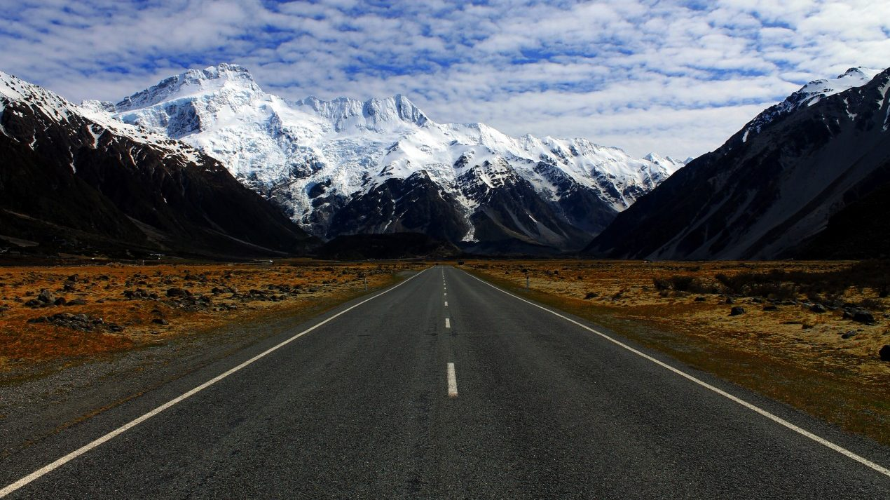 long stretch of highway with mountains in the distance
